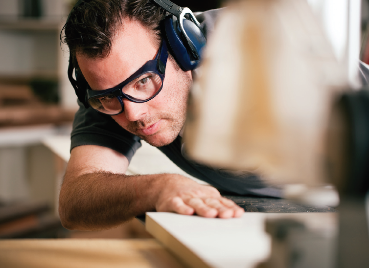 Wood Manufacturing worker at a plant cutting wood plies